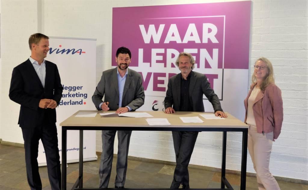 Rob van Vroenhoven (NIMA) links en Carlo Segers (FC) rechts achter de tafel,geflankeerd door Tom Valk (directeur School voor Commercie en Dienstverlening van het Friesland College) links en Baukje Hilarides (productmanager Study Members & Exams van NIMA) rechts.